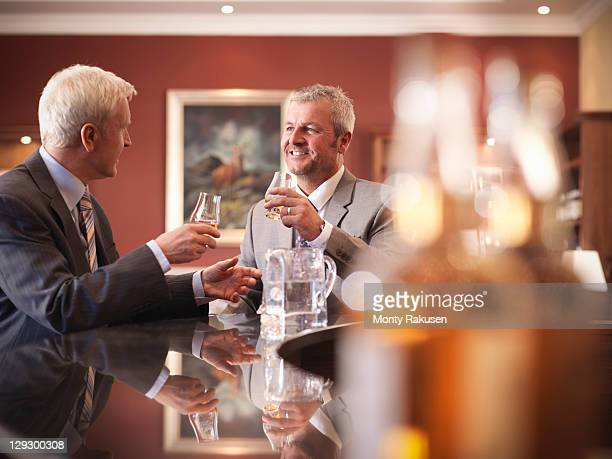 Business men drinking whisky at bar in lounge
