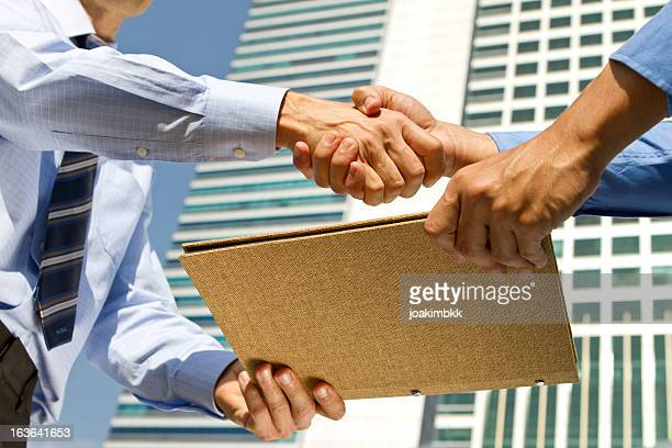 Business men handshaking and sharing file report in financial district