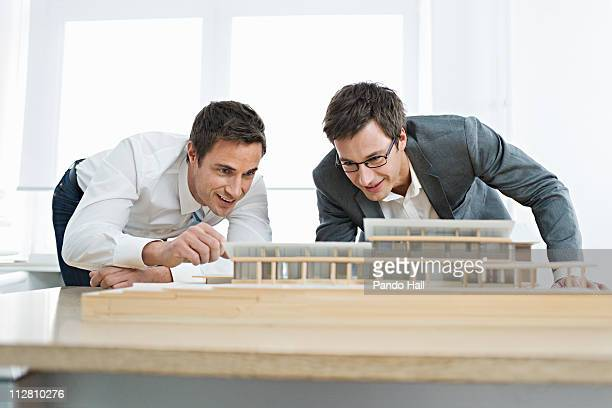 Business men looking at architectural model