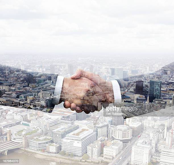 Business men shaking hands above city view.