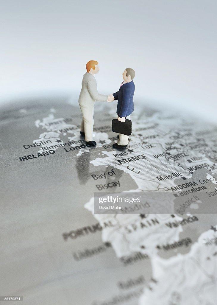 Business men shaking hands over globe : Stock Photo