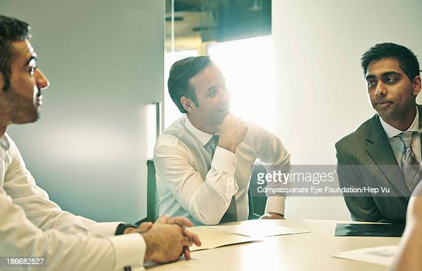 Business men sitting around meeting table