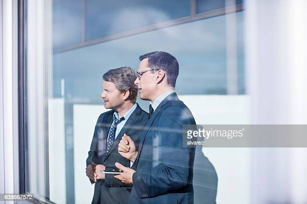 Business men standing together behind glass
