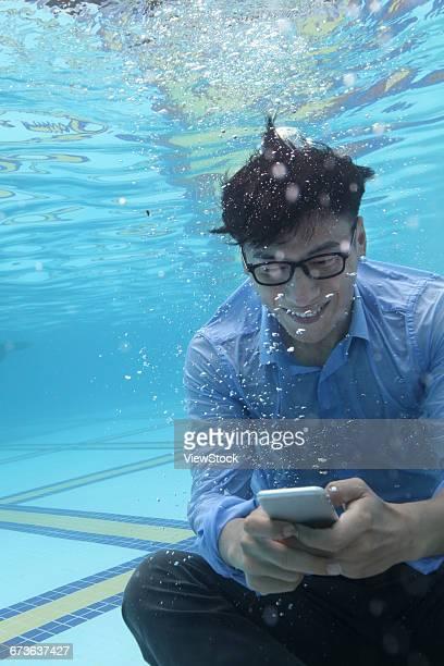 Business men use mobile phones under water