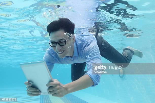Business men use tablet PCs under water
