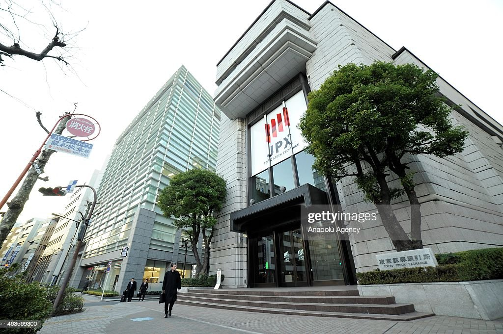 Business men walk in front of building of the Tokyo Stock Exchange in Tokyo Japan on February 16 2015 Japan's economy emerges from recession recently...