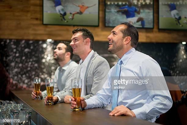 Business men watching football at a sports bar