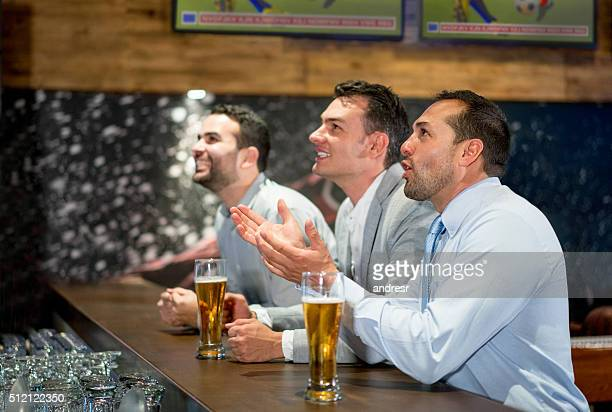 Business men watching football at a sports bar