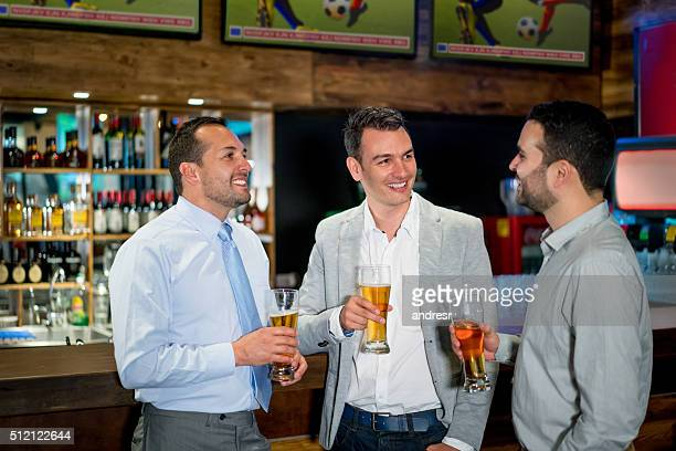 Business men watching sports at the bar after work