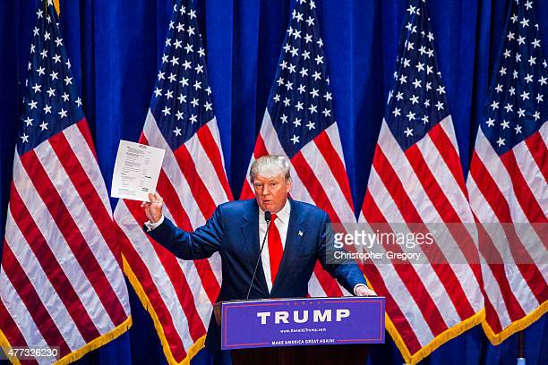 Business mogul Donald Trump holds documents certifying his net worth is 87 billion dollars as he announces his candidacy for the US presidency at...