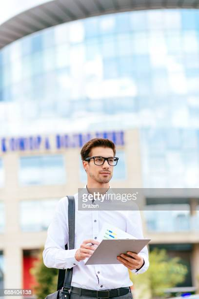 Business on the move - businessman in financial district using smartphone for communication