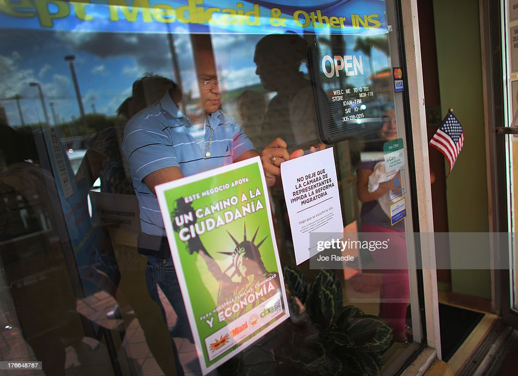 Business owner, Adam Miranda, tapes posters to his window in support of immigration reform after protesters stopped by his business to get his support in asking congress people to make immigration reform a reality on August 16, 2013 in Miami, Florida. The protesters were targeting Representatives Ileana Ros-Lehtinen and Mario Diaz-Balart to do more to win Comprehensive Immigration Reform with a path to citizenship.