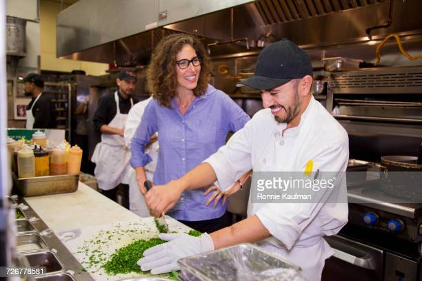 Business owner and chef laughing in restaurant