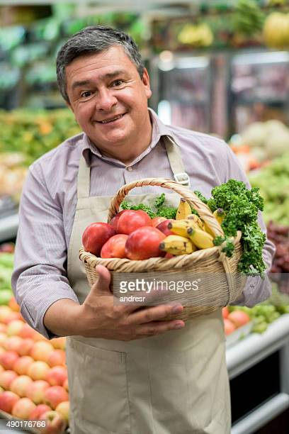 Business owner at a food market holding a basket