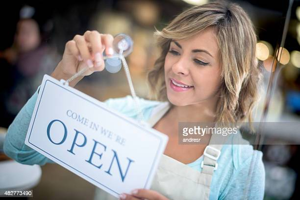 Business owner hanging an open sign at a store