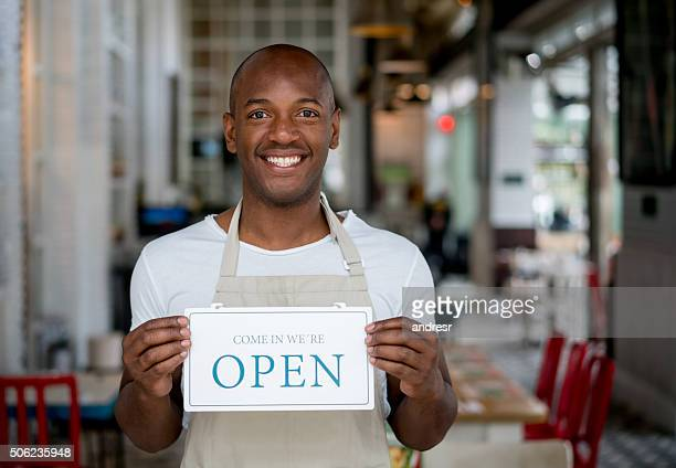 Business owner holding an open sign at a restaurant