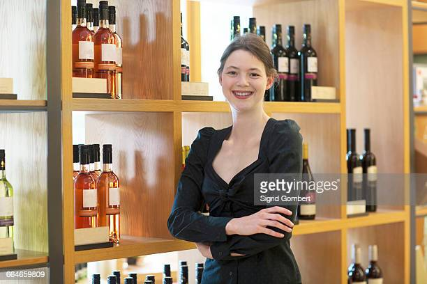 Business owner in wine shop arms crossed looking at camera smiling