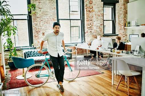 Business owner leaning against bicycle in office