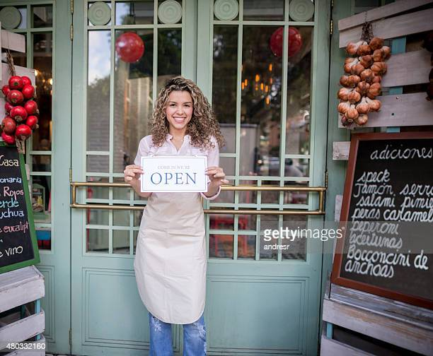 Business owner outside a market holding an open sign