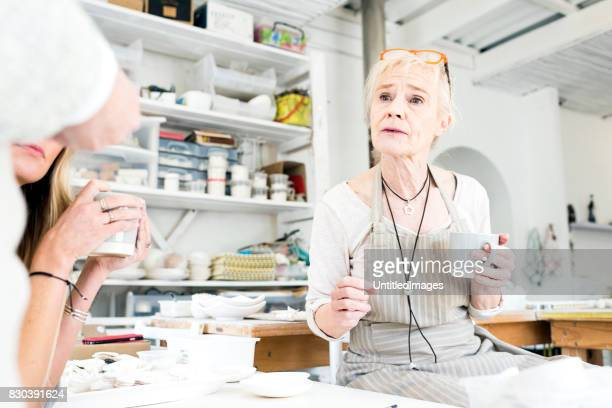 Business owner talking at workbench in workshop
