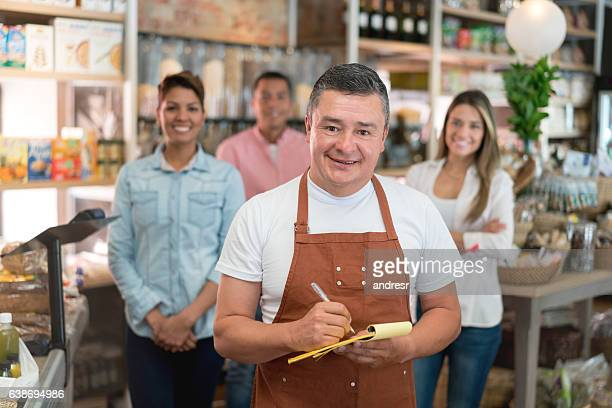 Business owner with customers at a grocery shop
