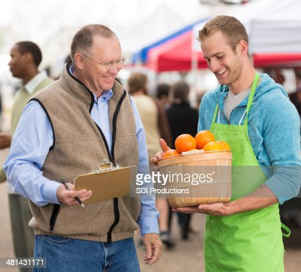 Business owner with employee checking produce at local farmers market