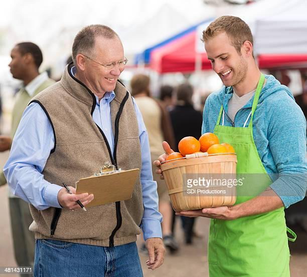 Geschäftsinhaber mit Mitarbeiter, die Produkte von lokalen Bauernmarkt