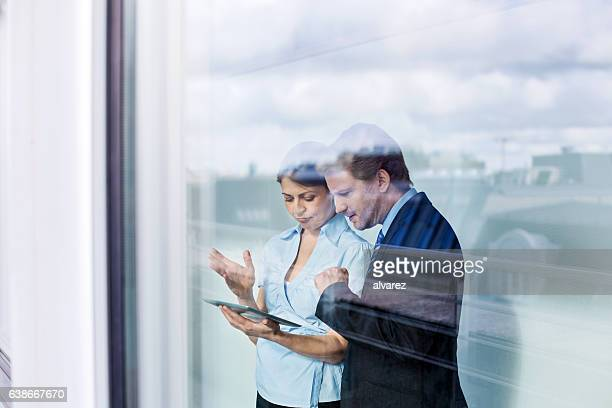 Business partners behind glass wall using digital tablet