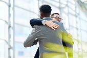 Portrait of two business partners hugging  and smiling with happiness standing in modern glass hall of office building