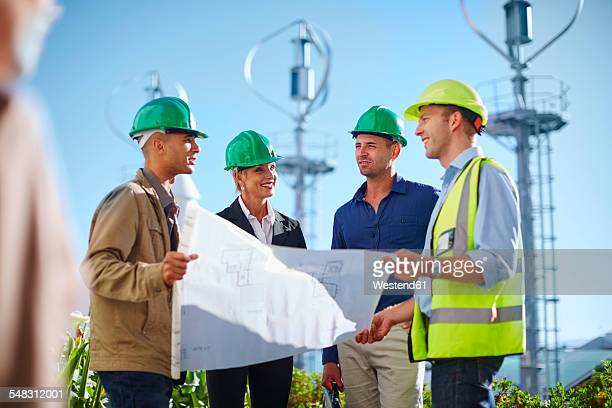 Business partners looking at wind turbine schematics with engineer
