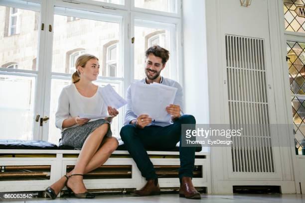 Geschäftspartner Sat Down durch Papierkram zusammen gehen