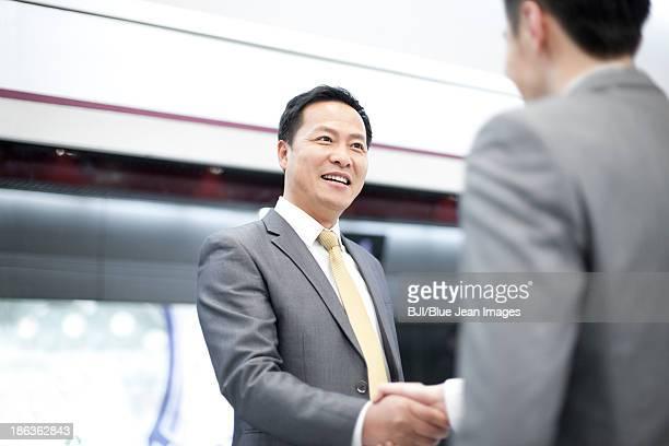 Business partners shaking hands on subway platform