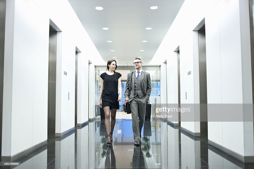 Business partners walking along office corridor