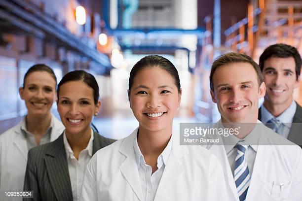 Geschäftsleute und Wissenschaftler stehen zusammen in Fabrik