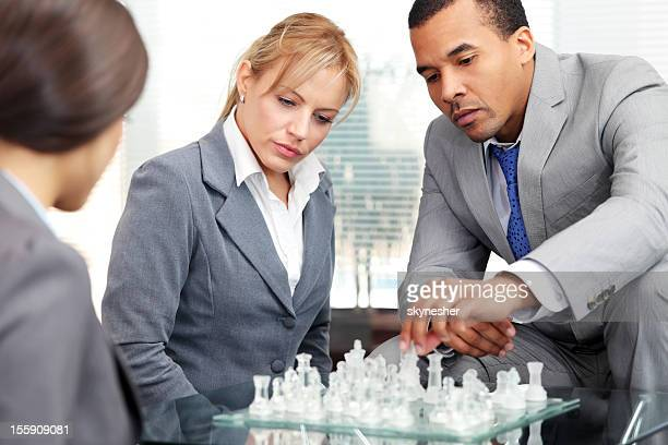 Business people are playing chess.
