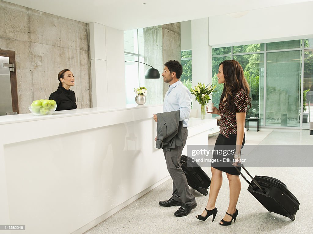 Business people arriving at hotel reception area : Stock Photo