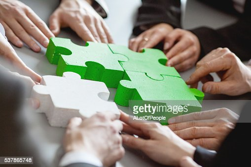 Business people assembling puzzle : Stock Photo