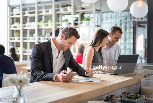 Business people at a cafe using technology