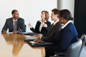 Business people at conference table, woman making hand gestures