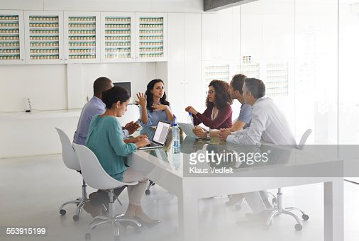 Business people at meeting, by glass table