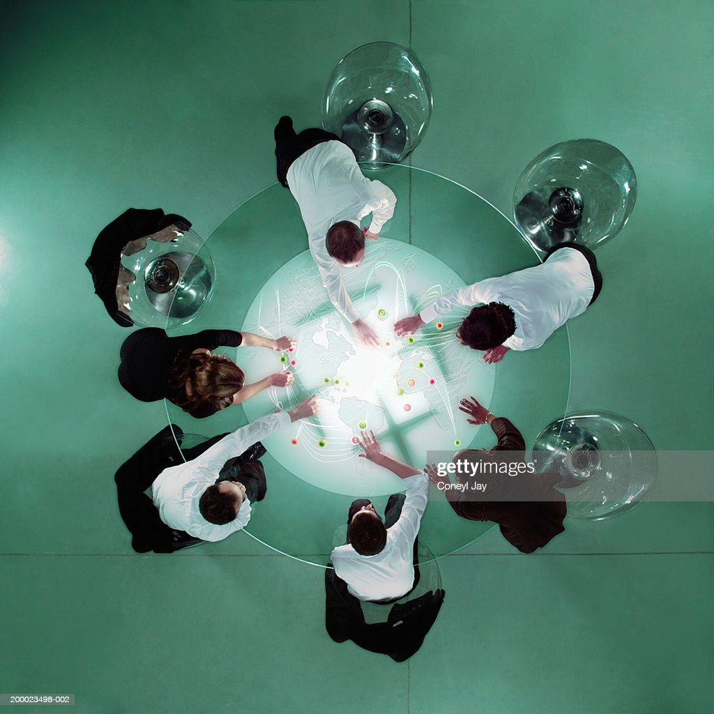 Business people at table placing markers on map, overhead view : Stock Photo