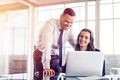 Young business woman showing information on laptop to businessman. Beautiful businesswoman explaining plan to businessman on computer. Colleagues working together in modern office.