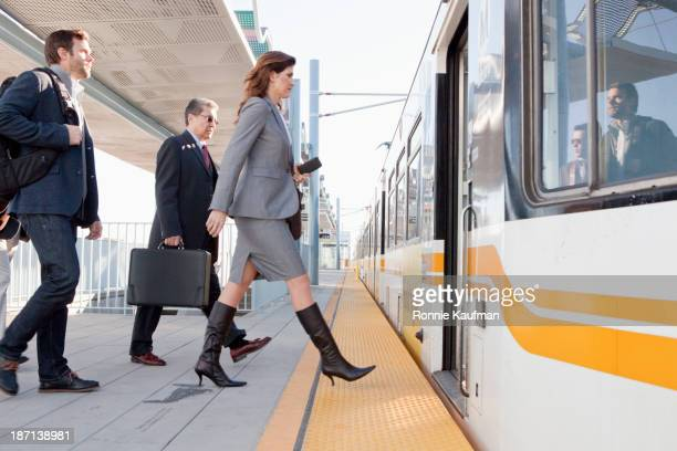 Business people boarding train in station
