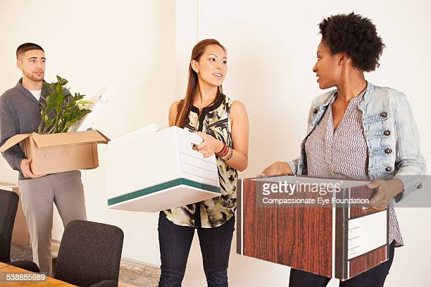 Business people carrying boxes in office