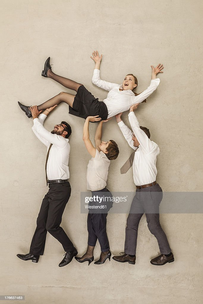Business people carrying businesswoman in office : Stock Photo