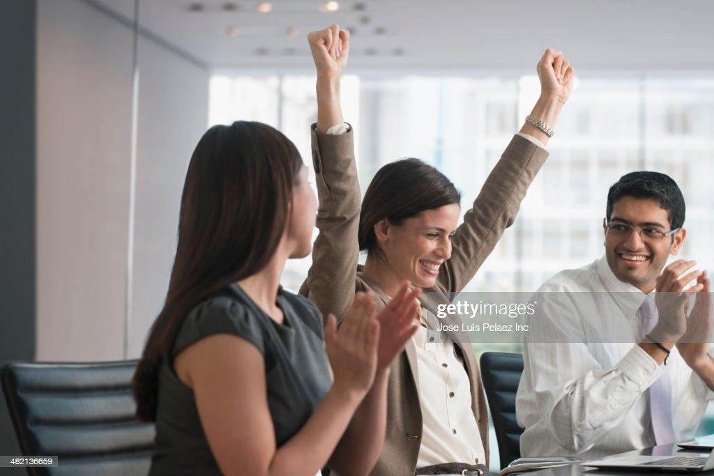 Business people cheering in meeting