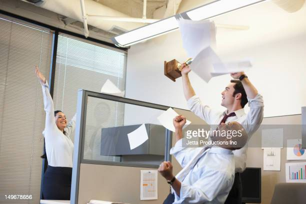 Business people cheering in office cubicle