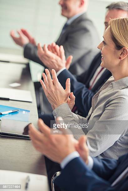 Business people clapping at a meeting