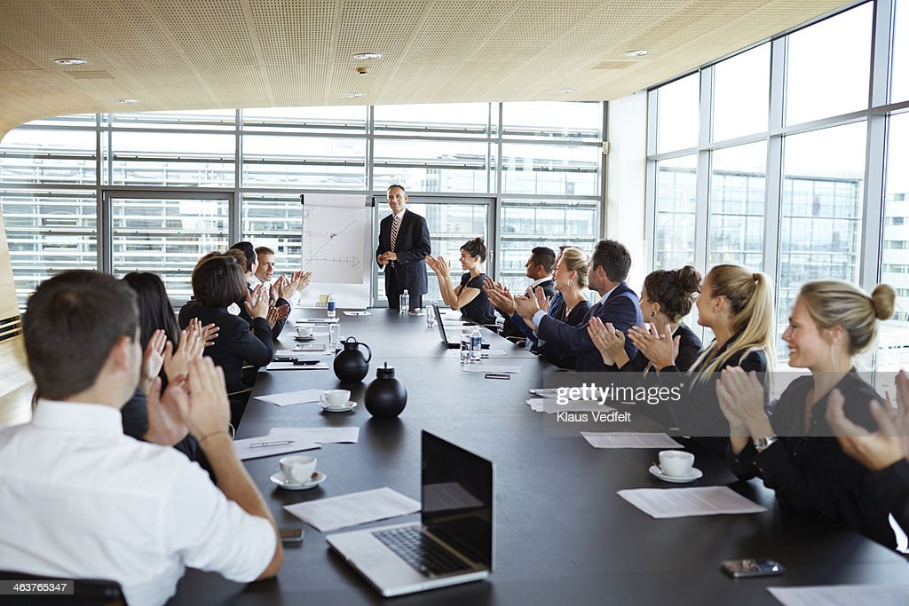 Business people clapping at big presentation