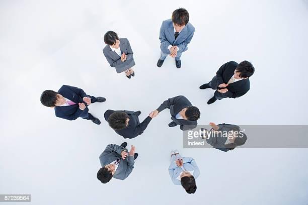 Business people clapping for two men shaking hands